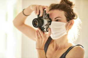 eine junge Frau mit Maske, die eine Spiegelreflexkamera im Anschlag hat.
