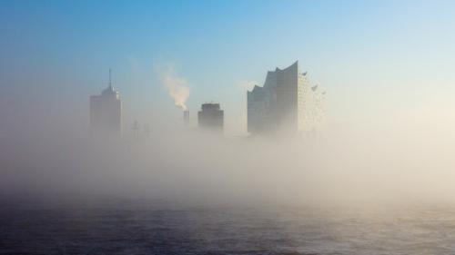 man sieht die Elbphilharmonie im Nebel