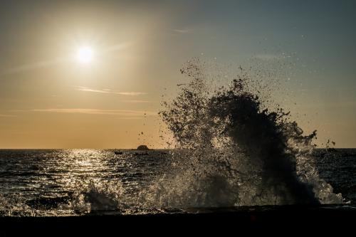 Man sieht das Meerwasser, wie es sich an einer Barriere bricht und sich aufbäumt.
