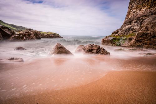Das ist ein Strand mit Felsen und Meer